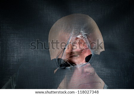 A peeping tom looking through a torn window screen in a creepy moment. - stock photo