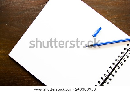 a pen and blank paper on the wood background - stock photo