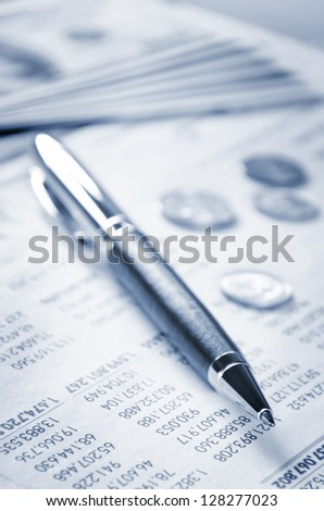 A pen and US currency on the paper of statement