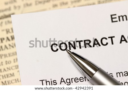 "A pen points to the words, "" contract"". Narrow depth of field highlights the pen."