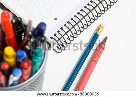 A pencil, pen and notepad with a pencil-holder in the foreground