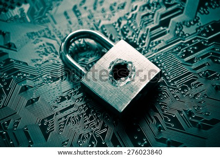 A penetrated security lock with a hole on computer circuit board background - stock photo