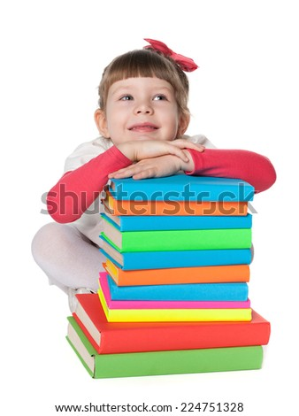 A pensive little girl is sitting on the floor near the pile of books on the white background