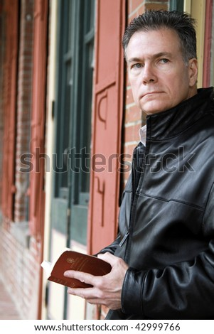 A pensive man holding a New Testament bible, standing by a building with colorful windowpanes and shutters.