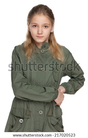 A pensive preteen girl in the green coat on the white background