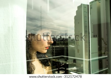A pensive vintage girl standing behind a window. - stock photo