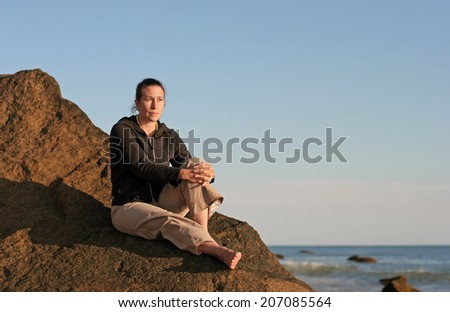A pensive woman sits on a large rock at a beach while looking out over the ocean. - stock photo