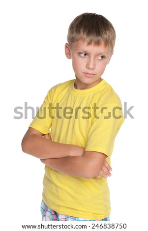 A pensive young boy in a yellow shirt looks aside against the white background