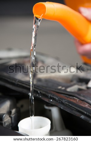 A People is refilling the water tank from his car. - stock photo