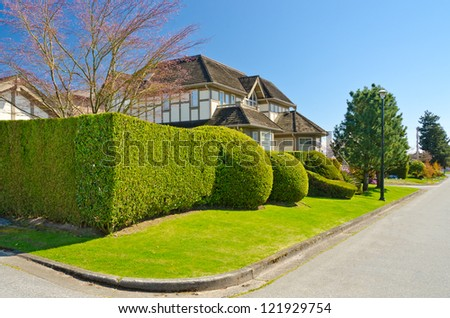 A perfect neighborhood. Houses behind green fences in suburb at Spring in the north America - stock photo