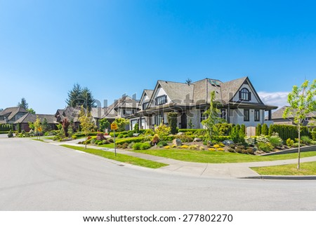 A perfect neighborhood on a sunny day with blue sky. Houses and townhouses in suburbs at Spring in the north America. - stock photo