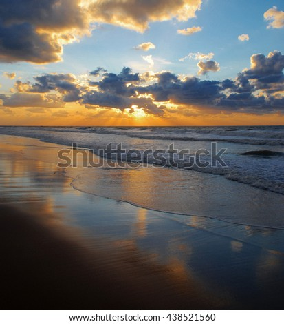 A perfect sunburst along a magic beach. - stock photo
