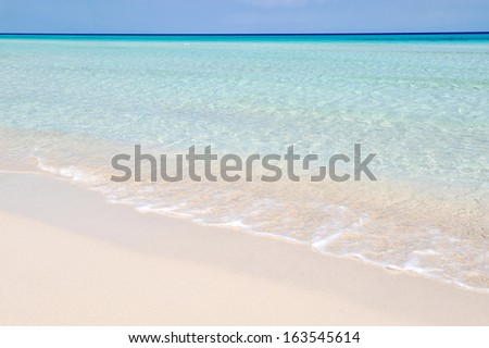 A perfect view of the sea. A line of blue cloudless sky, a thin line of dark blue water, a big  portion of of turquoise water, a portion of transparent water, and white sand, both wet and dry. - stock photo