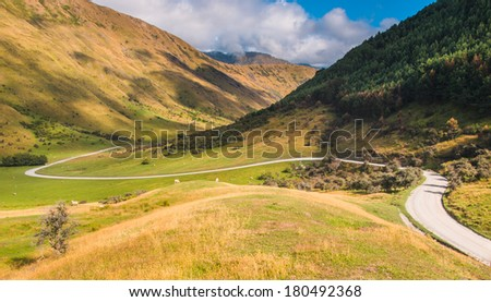 a perfect winding road through the New Zealand hills, Near Queenstown, Otago - stock photo