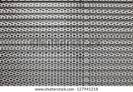 A perforated decorative metal grate for textural background. - stock photo