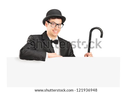 A performer in black suit, retro hat and cane posing behing a blank panel isolated on white - stock photo