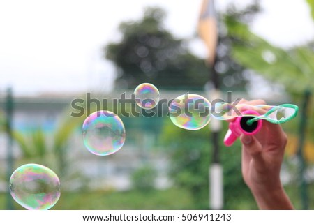 A person blowing soap bubbles in a park with blurred background - selected focus - depth of field