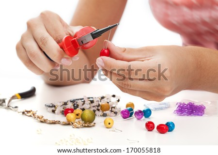 A person designing colorful earings with plactic beads - stock photo