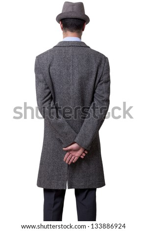 A person dressed in a gray overcoat and a gray hat standing with his back to the camera, holding his right hand over his left one.  Isolated on white background. - stock photo
