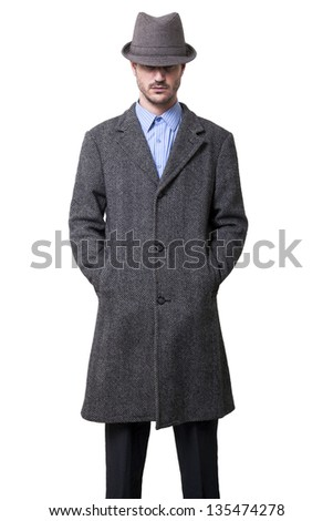 A person dressed in a gray overcoat and a gray hat that is almost completely hiding his eyes. Hands in coat pockets. Isolated on white background. - stock photo
