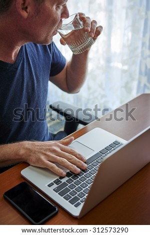 a person drinking water and working with a laptop - stock photo
