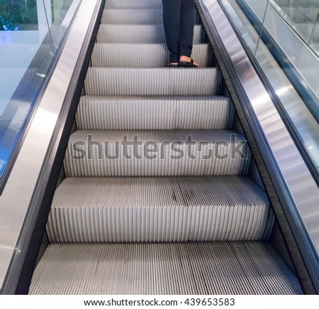 A person feet on an Old Escaltor travelling upward.