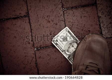 A person finds a US five dollar bill at the street and he uses his foot to step on it. - stock photo