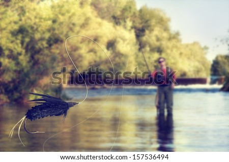 a person fly fishing in a river with a fly in the foreground - stock photo