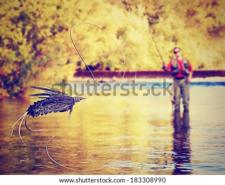 a person fly fishing with a big fly in front done with a soft vintage instagram like filter - stock photo