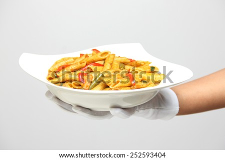 A person holding a bowl of pasta with pepper sauce - stock photo