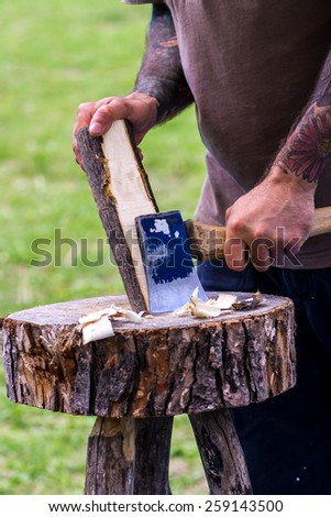 A person holding a piece of Wood, and working with an axe to transform it in a wooden stool. - stock photo
