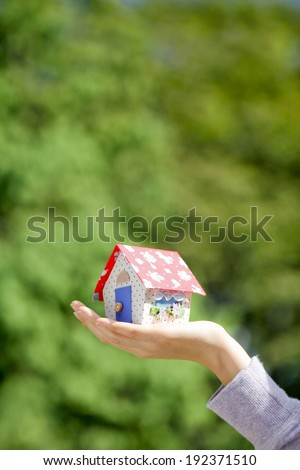 A person holding a small toy house in their hand. - stock photo