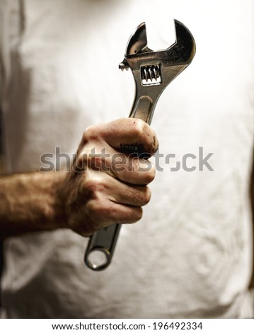 A person holding a wrench in their hand. - stock photo