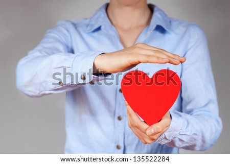 a person holding and protecting a heart symbolizing safety, love and health - stock photo