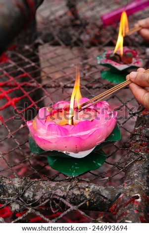 A person holding incense kindled in the lotus lamp - stock photo