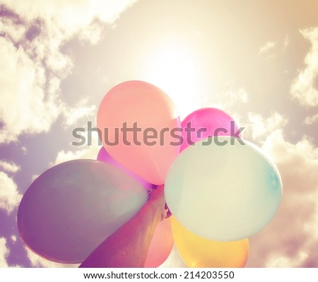 a person holding multi colored balloons done with a retro vintage instagram filter effect - stock photo