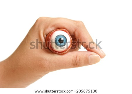 A person holds an eyeball in their hand. - stock photo