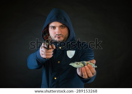 A person in a hoodie is aiming and holding the other hand with the dollar note. A concept of the robbery.
