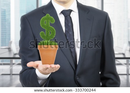 A person in formal suit holds a flowerpot with grass green dollar sign. Office open space in blur on the background.