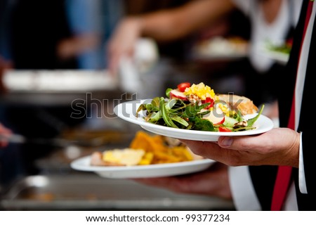 a person in line with their food during a banquet or other catered event - stock photo