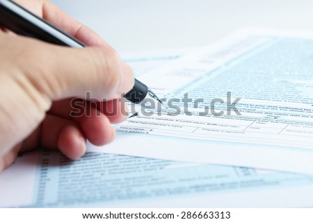 A person is completing the tax form with a pen.