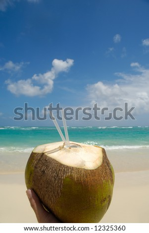 A person is holding an coconut drink on an exotic beach with blue and cloudy sky