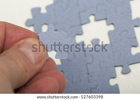 A person is putting the missing piece on a puzzle.