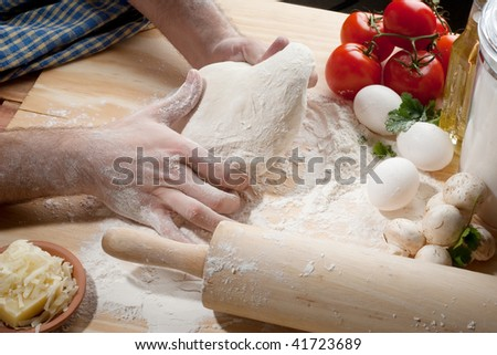 A person kneading dough on table top with fresh tomatoes, flour and cheese - stock photo