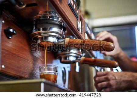 a person making espresso at a coffee shop - stock photo