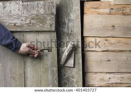 a person opens an old wooden door with a latch
