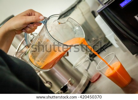 A person pouring smoothie from a blender into a plastic cup - stock photo