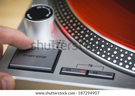 a person pressing the stop button of a record player