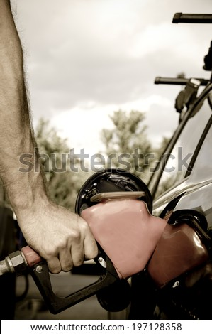A person pumping gas into their car on an overcast day. - stock photo
