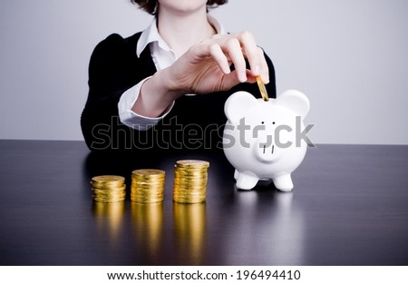 A person putting gold coins into a piggy bank with stacks beside it. - stock photo